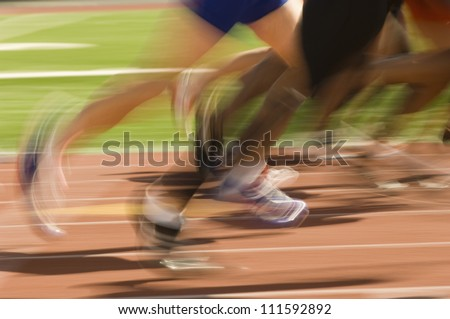 Blurred motion of male athletes racing - stock photo