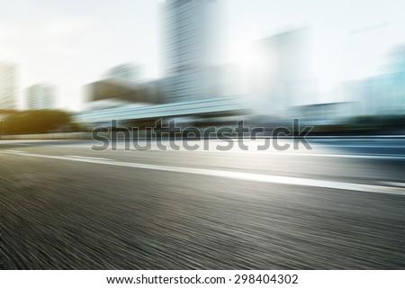 Blurred motion of modern skyline and urban street  - stock photo