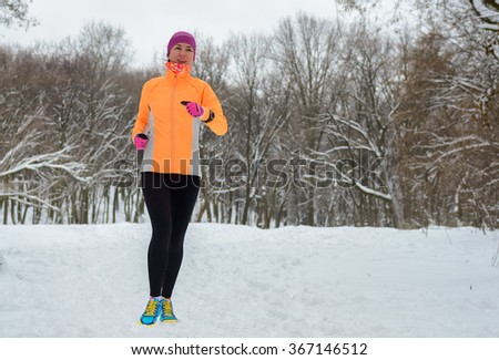 Blurred motion: winter running in forest, happy woman runner jogging in snow, outdoor sport and fitness concept  - stock photo