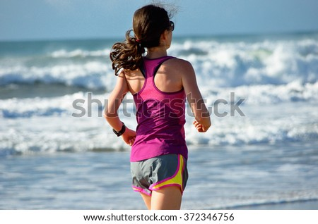 Blurred motion: woman running on beach, beautiful girl runner jogging outdoors, training for marathon, exercising and fitness concept  - stock photo