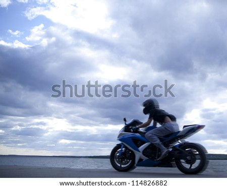 blurred motorcyclist against blue sunset - stock photo