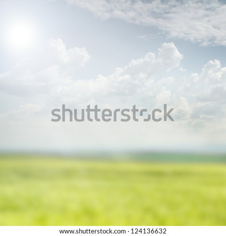 Blurred nature background | green field with sunny sky covered in clouds - stock photo