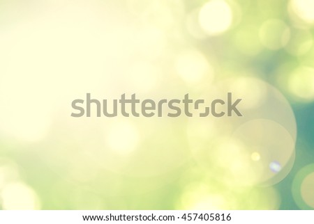 Blurred nature background of a view looking up through the foliage of tree against the sky facing sun flare and bokeh: Blurry natural greenery wood forest view in bright green lime yellow color tone - stock photo