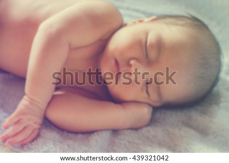 blurred newborn cute Asian baby boy sleeping with blue blanket in vintage and color filter tone style : people concept - stock photo