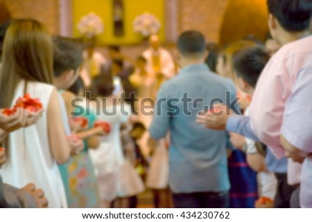 Blurred  Newlyweds coming out of the church after wedding ceremony under the rain of rose petals. - stock photo