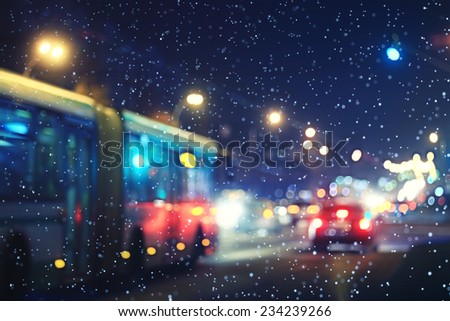 blurred night background city traffic road city lights winter snow glare - stock photo
