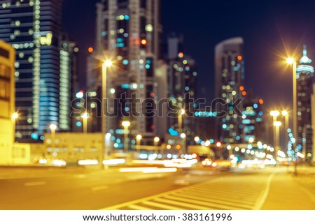 Blurred nighttime cityscape with illuminated modern architecture and street lights. Downtown Dubai, UAE. - stock photo