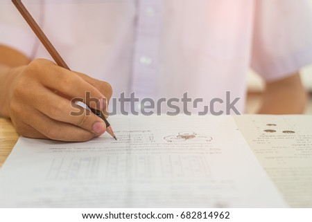 Blurred of Asian boy students hand holding pencil writing fill in Exams paper sheet or test papers Mathematics on wood desk table with student uniform in exam class room, education concept