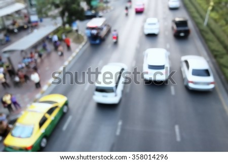 Blurred of cars in traffic with people at bus stop
