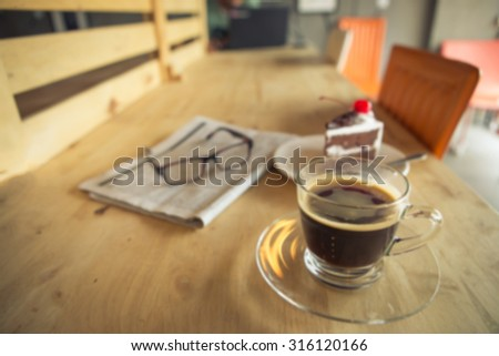 Blurred of cup of coffee with newspaper - stock photo