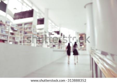 blurred office women walking through hallway passing book store background - stock photo