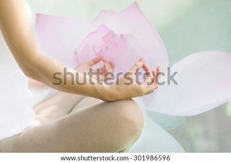 Blurred pastel image of healthy female in yoga pose. Peace, zen and inner harmony concept. Lotus flower in the background. - stock photo