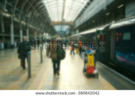 Blurred people at a railway station traveling by train - stock photo