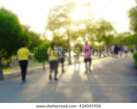 Blurred People exercising in the city park by jogging, walking, running, bicycling for better health and strong body and mind. - stock photo