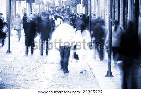 Blurred people in the middle of the street - stock photo