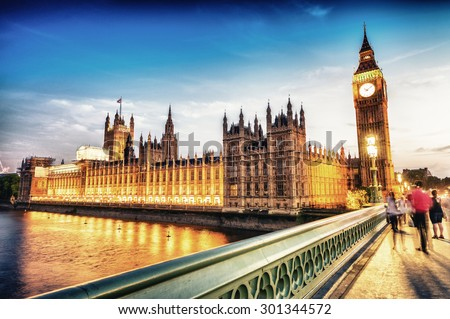 Blurred people moving at night on Westminster Bridge, London. - stock photo