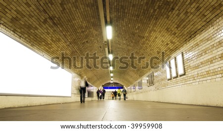 Blurred people on city underground tunnel - stock photo
