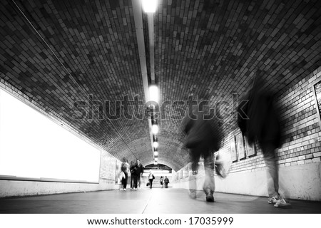Blurred people on tunnel, black and white. - stock photo