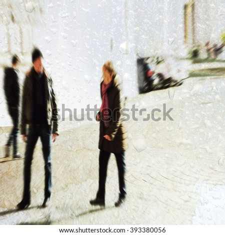 blurred people walking in the street behind wet glass. Out of focus technique.