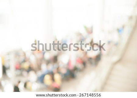 Blurred photo of an airport terminal with unrecognizible passengers passing by with luggage. Blurred background for topics of travel and transportation. - stock photo
