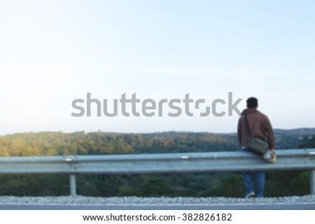 Blurred photo of Asian man sitting on the side of mountain road