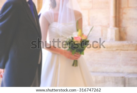 Blurred photo of bride and her father waiting before entering to the church on wedding day (father is taking his young daughter to the altar). Toned image. - stock photo