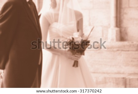 Blurred photo of bride and her father waiting before entering to the Gothic church on wedding day (father is taking his young daughter to the altar). Sepia. - stock photo