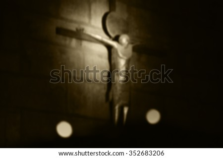 Blurred photo of crucifix on the stone wall and the candles at foreground. Symbolic contrast of light and darkness. Aged photo. Sepia. - stock photo