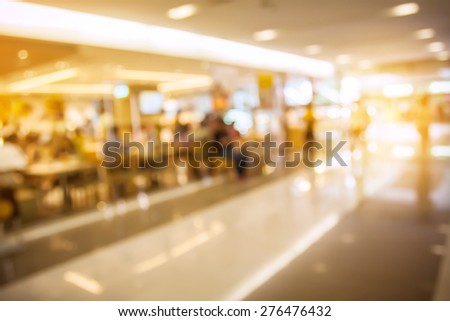blurred photo of people walking in shopping center with filtered color effect. - stock photo