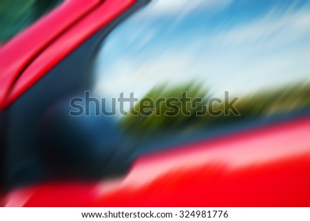 Blurred photo of rural landscape reflected in side window of a red car. - stock photo