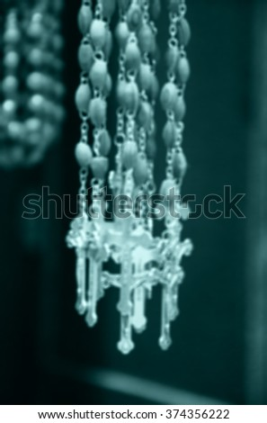 Blurred photo of wooden rosary beads with silver crucifix. Toned image. - stock photo