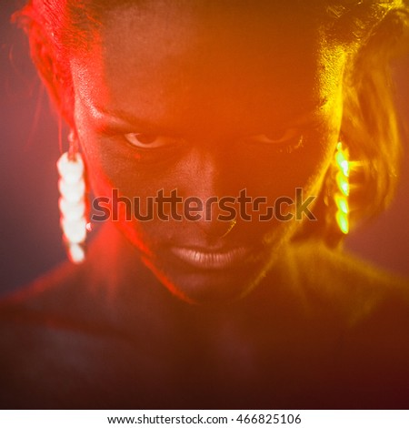 Blurred picture of black angry woman's face covered with red and green light