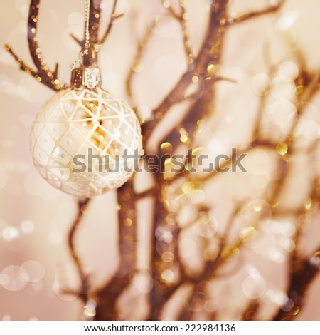Blurred picture of white snowy Christmas decoration with baubles on the branch. Nice bokeh lights, instagram vintage effect. - stock photo