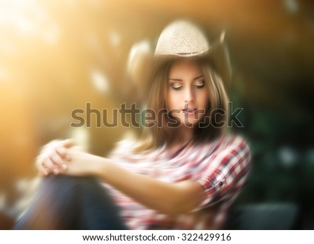 Blurred portrait of sexy cowgirl in sun light. Young woman in a hat - stock photo