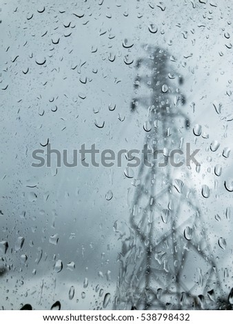 Blurred rain drop on the car glass background, water drops at the car window driver side, blurred high voltage pole , low saturated color
