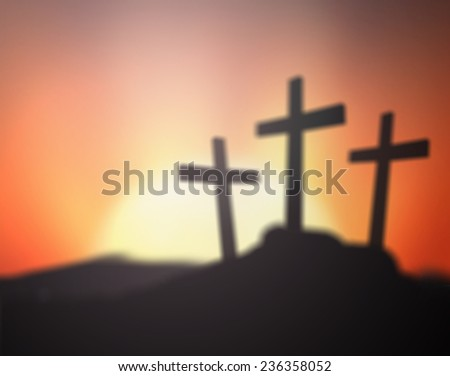 Blurred silhouette impression of the three crosses on the mountain golgotha representing the day of christs crucifixion in a sunset. Christmas background, Worship, Forgiveness, Thanksgiving concept.