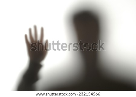 blurred silhouette of a man with his hand up