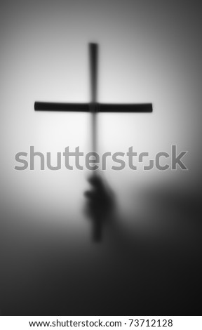 Blurred silhouette of hand with cross in the dark
