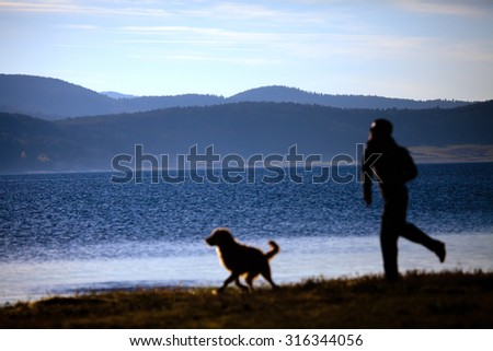 blurred silhouette of man and dog playing near high mountain lake  - stock photo