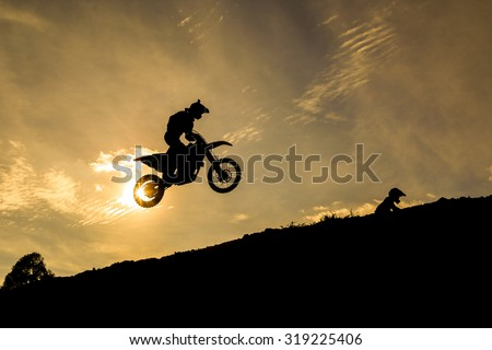 Blurred silhouette of motocross rider jumping on the mountain in sunset
