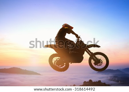 Blurred silhouette of motor cross rider jumping on the mountain in sunrise