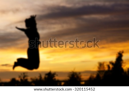 Blurred silhouette woman jump. sunset background - stock photo