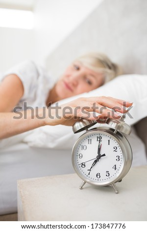 Blurred sleepy mature woman extending hand to alarm clock in bed at home - stock photo