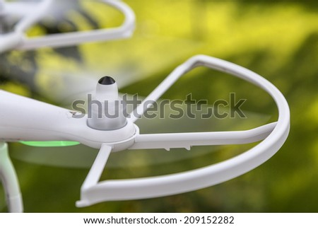 blurred spinning propellers of a small helicopter drone (quadcopter) flying over green grassy surface, focus on a propeller hub - stock photo