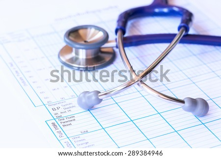 Blurred stethoscope and patient record chart.Medical concept. - stock photo