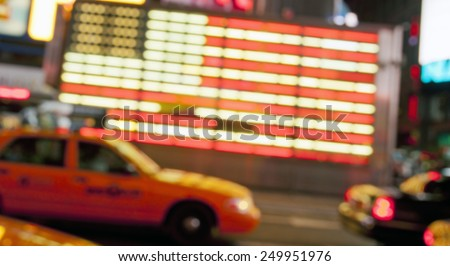 blurred street lights of neon US flag and yellow cab at Times Square in New York City in the night, abstract background - stock photo