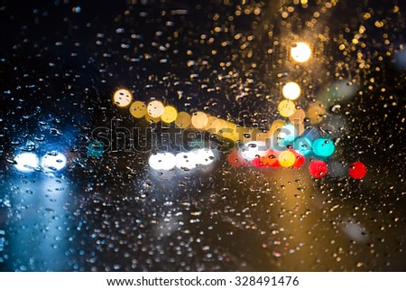 blurred traffic viewed through a car windscreen covered in rain - stock photo