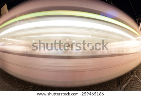 blurred tram in Freiburg at night  - stock photo