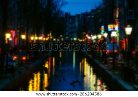 Blurred travel backgrounds. Night view of Red - light district in Amsterdam, Netherlands, where is a concentration of sex shops, strip clubs, adult theaters, etc