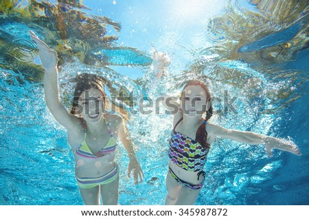 Blurred underwater: children swim in pool or sea, happy active girls have fun in water, kids sport on family vacation  - stock photo